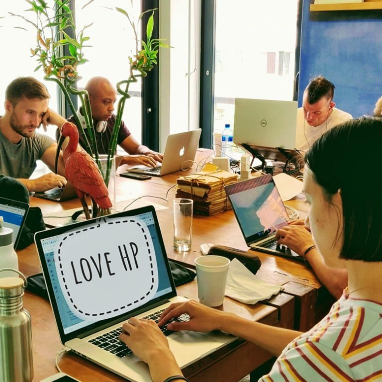 Remote workers in Cape Town, South Africa work on their laptops in the coworking space