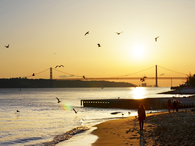 Travelers enjoying the sunrise on the peaceful beach in Lisbon, Portugal
