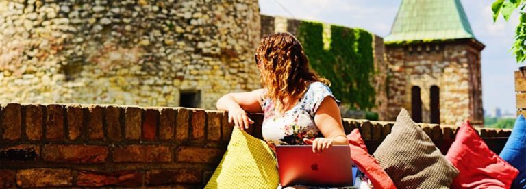 Girl Working on her laptop in Belgrade with a view of a castle in the background
